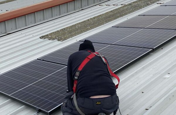 Island renewables employee fitting solar PV on seacat services roof